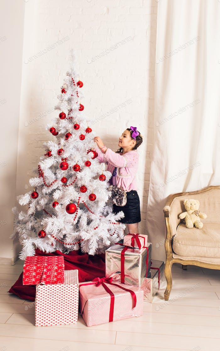 8 years old little girl decorating Christmas tree at home.