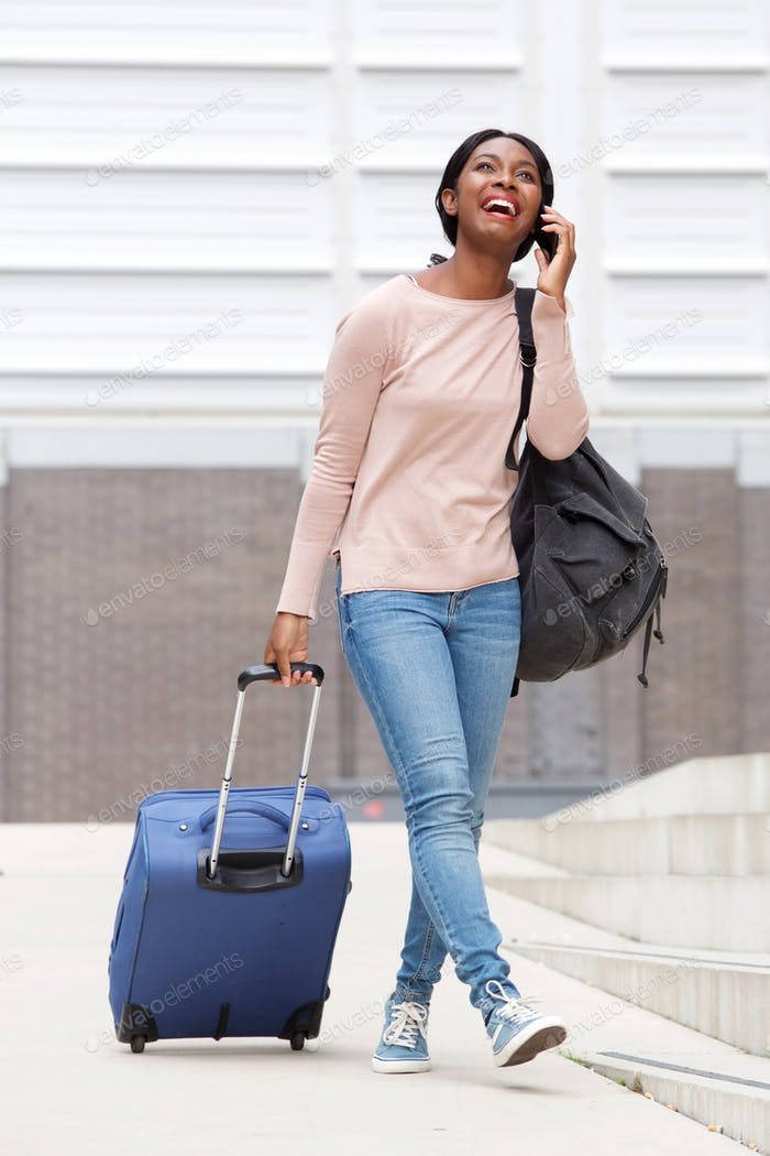 Full body happy young african american woman walking with suitcase bag and mobile phone