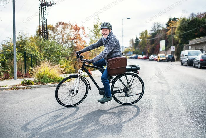 Active senior man with electrobike cycling outdoors in town.