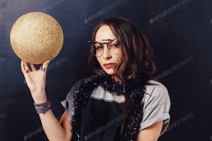 Portrait of seductive hipster girl holding a gold discoball