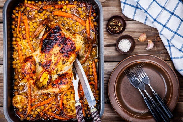 Roasted whole chicken with chickpeas, carrots and lemons
