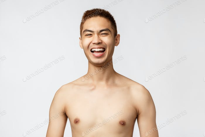 Beauty, people and home concept. Close-up portrait of handsome cheerful asian man, laughing out loud