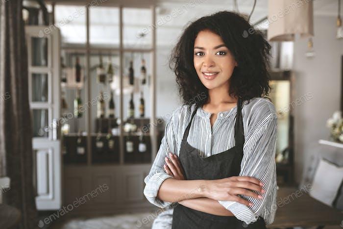 Vertical de hermosa niña afroamericana con camisa y delantal en Restaurante