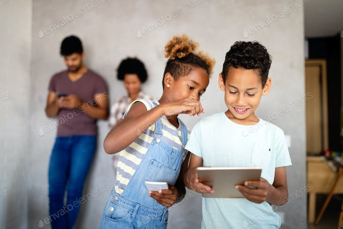 Happy african american family using technical devices, phone. tablet