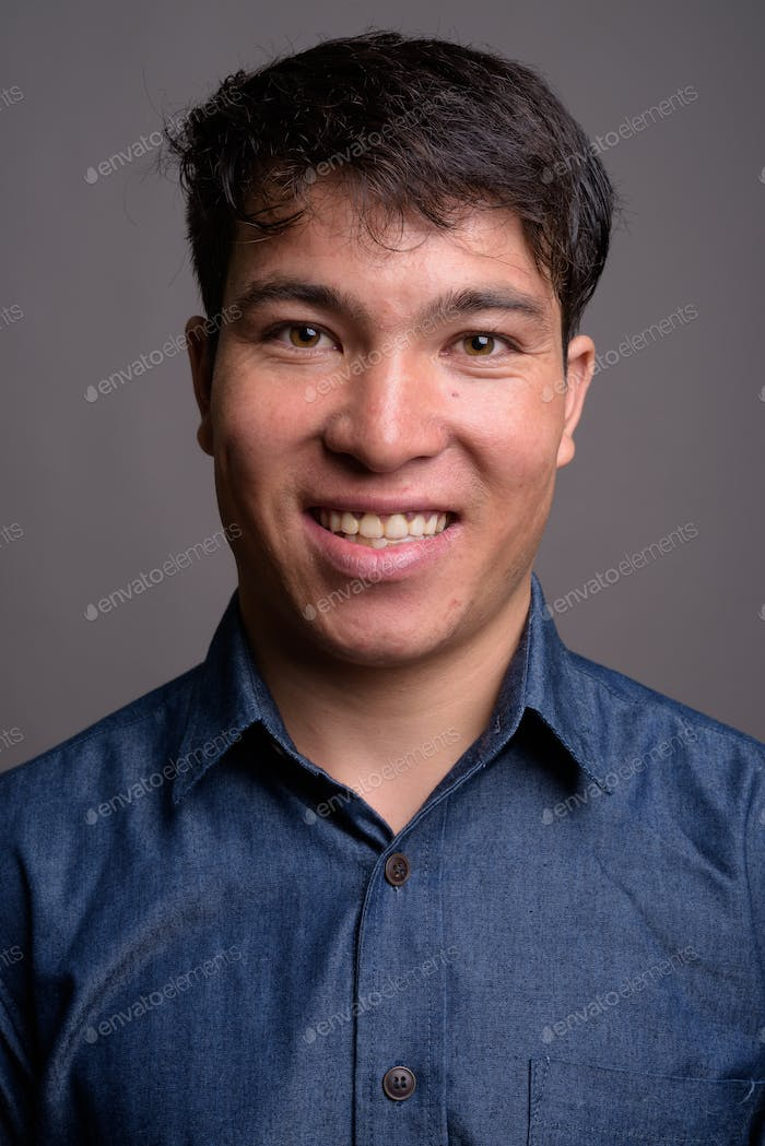 Young Asian man wearing blue shirt against gray background
