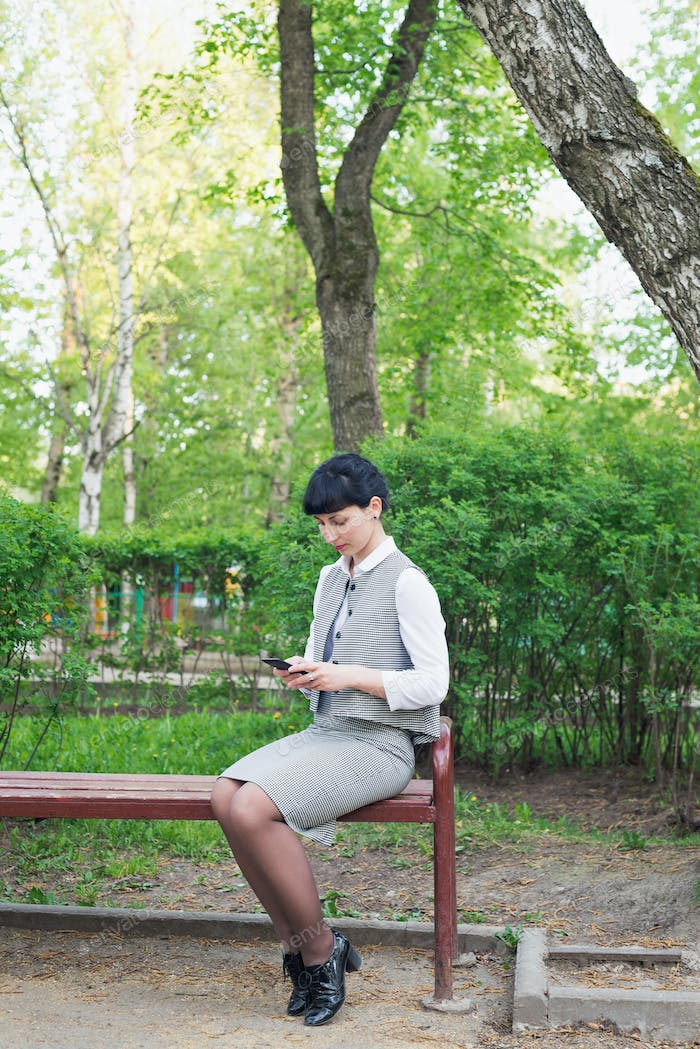 woman sits in business clothing on bench