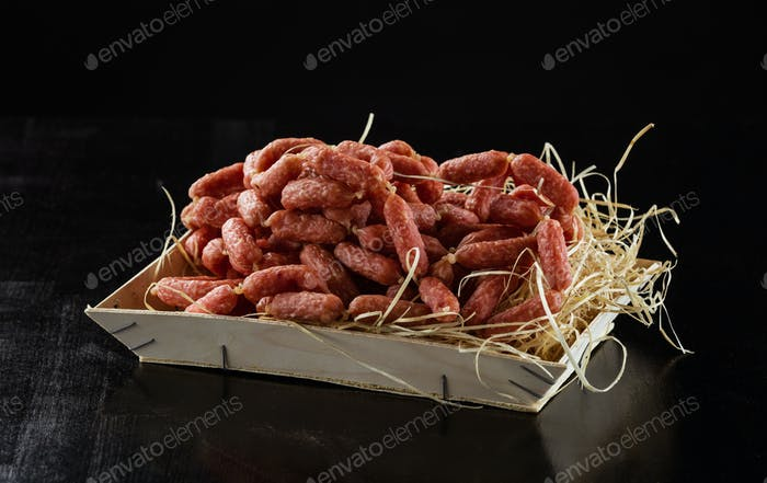 Picnic salami sausages in wooden box over black