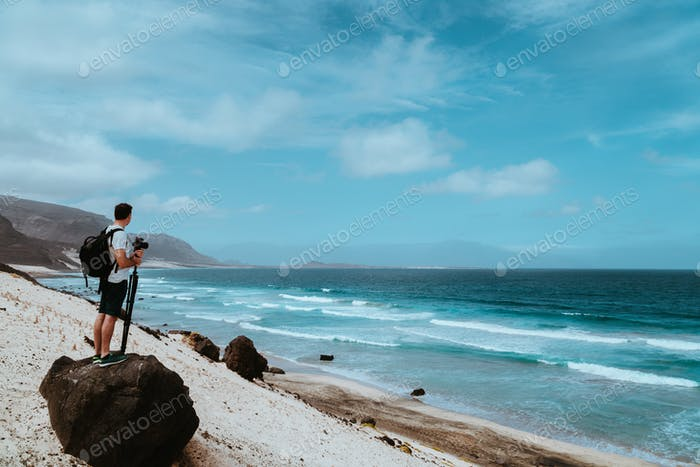 Photographer with stative and camera staying on the rock and enjoying coastal landscape of sand