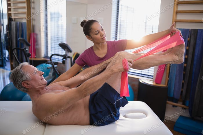 Female therapist looking at male patient pulling resistance band while lying on bed