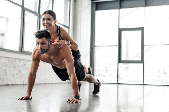 muscular bare-chested sportsman doing push ups with smiling sporty girl on back in gym