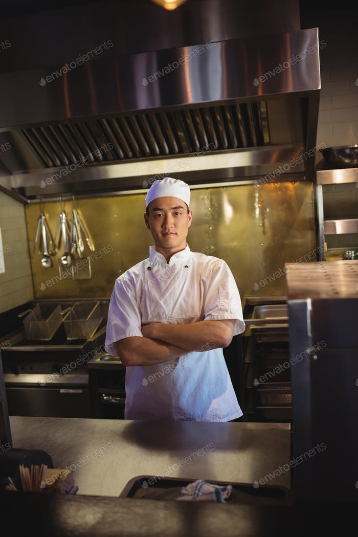 Smiling chef standing with arms crossed in the commercial kitchen