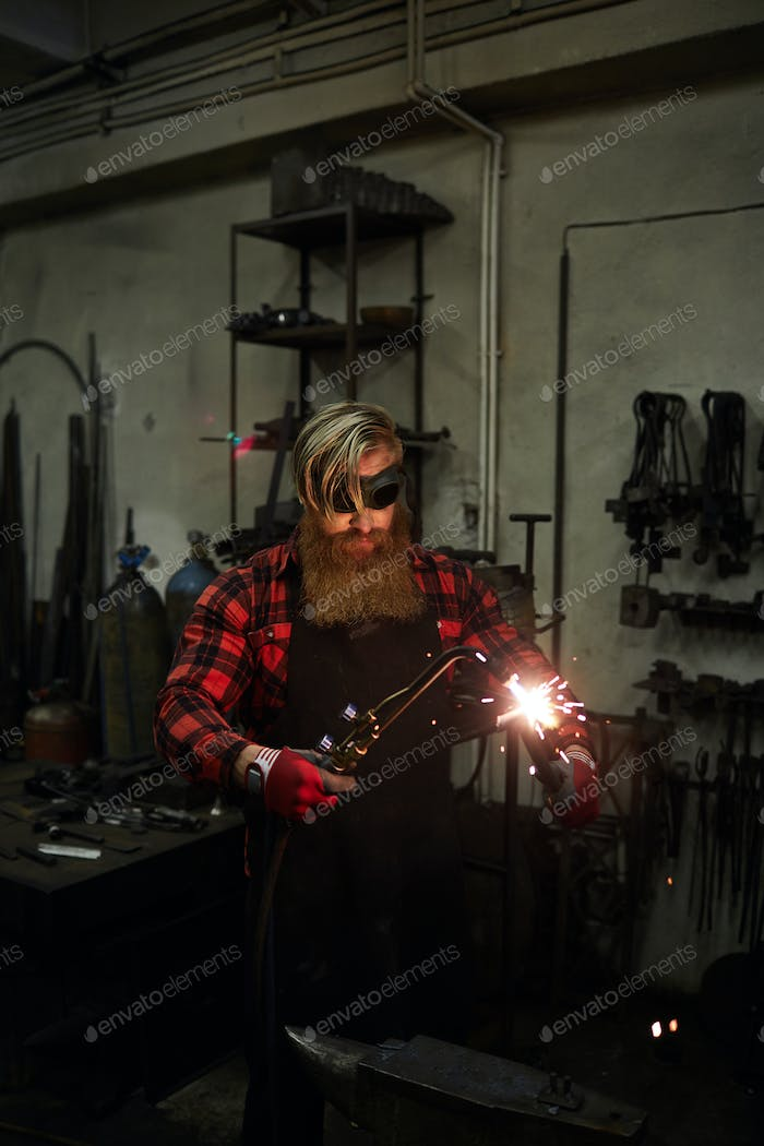 Cutting steel with torch in workshop