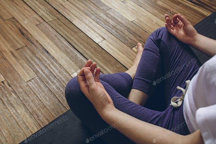 Woman practicing yoga doing Half Lotus pose with mudra