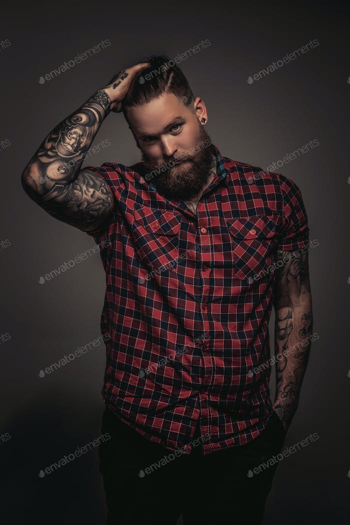 Man with beard and tattoo holding his head.