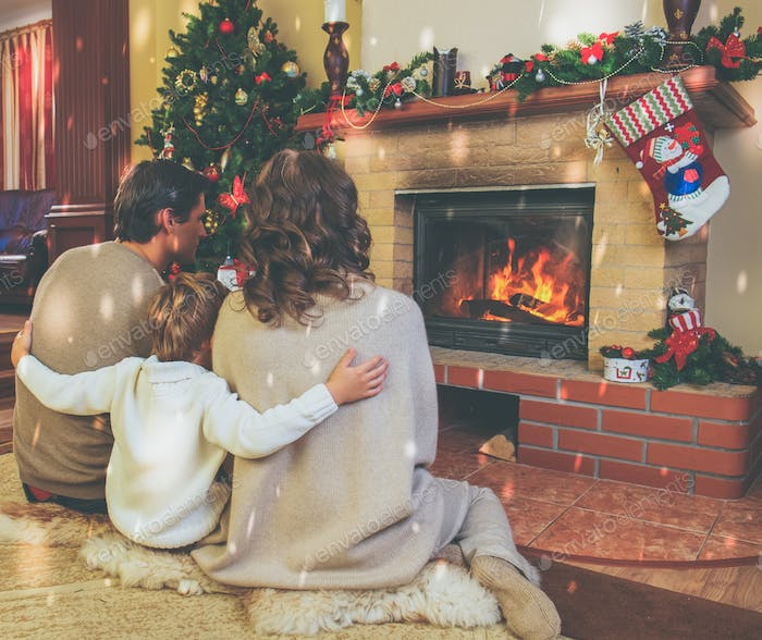 Family near fireplace in decorated house interior