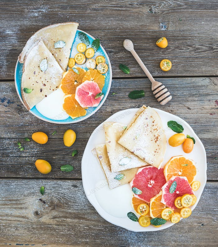 Spring vitamin breakfast set. Thin crepes or pancakes with fresh grapefruit, orange