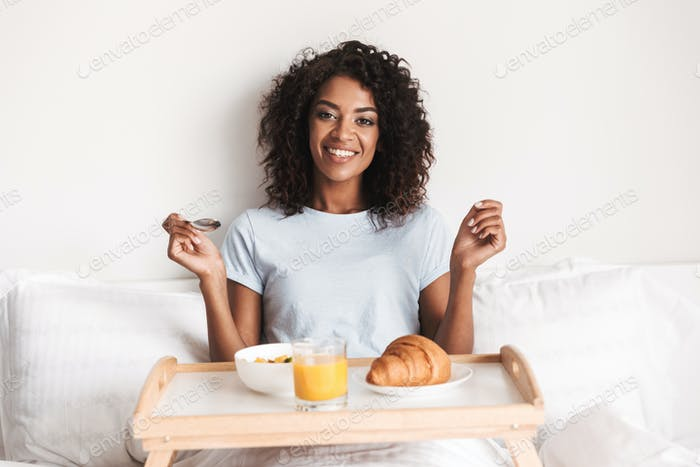 Happy young african woman having tasty breakfast