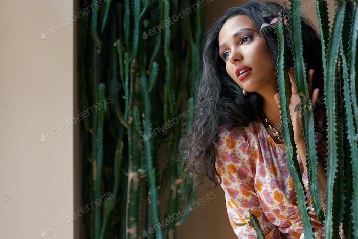 Portrait of mulatto female model among cactuses