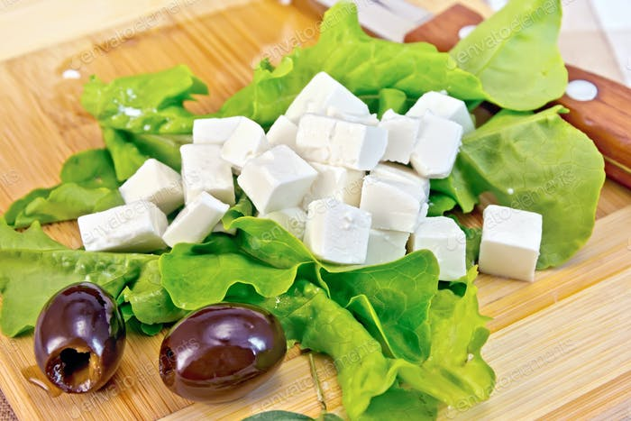 Feta with olives and green lettuce on board