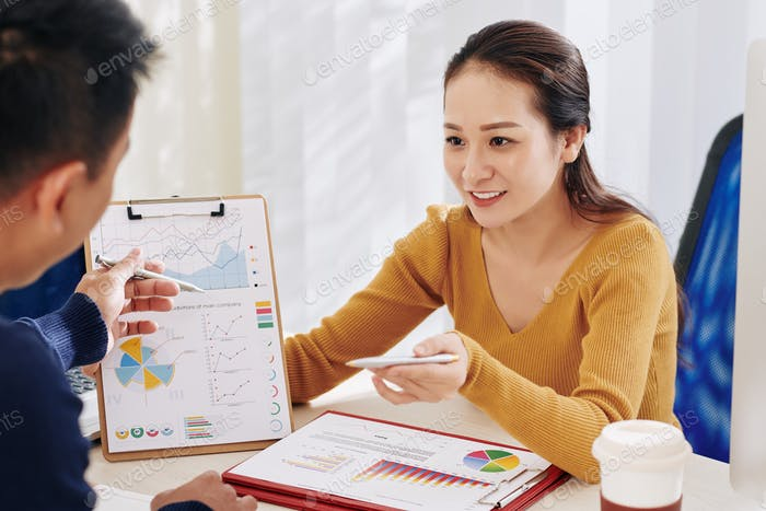 Businesswoman showing document to colleague