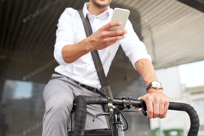 Mann mit Smartphone und festen Gear Fahrrad auf der Straße