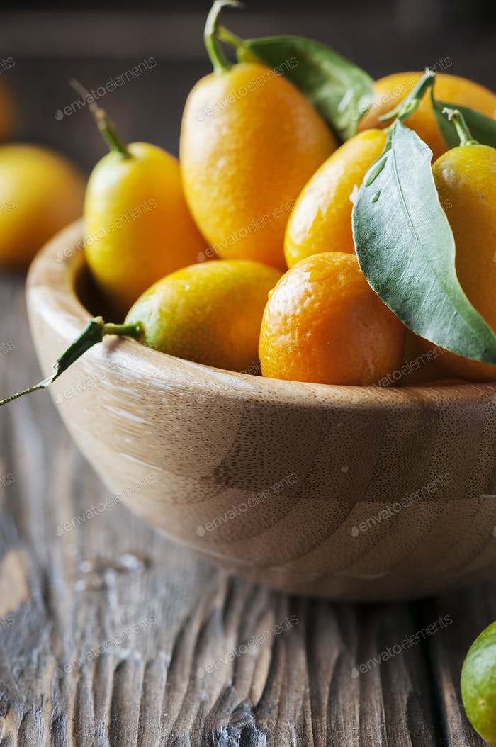 Fresh kumquat with green leaves on the wooden table