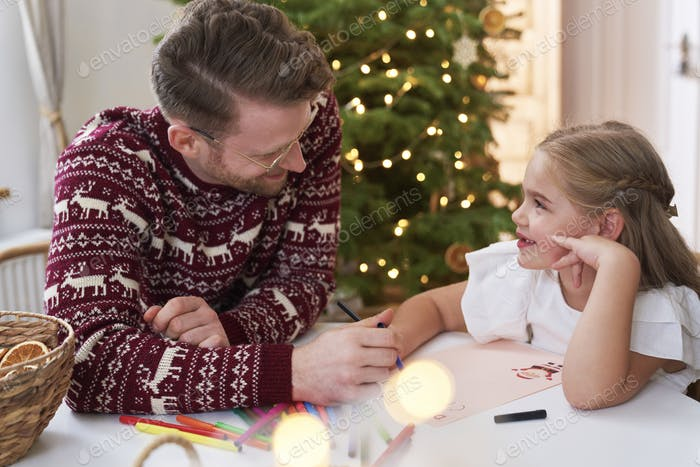 Little girl writing letter to Santa Claus with daddy