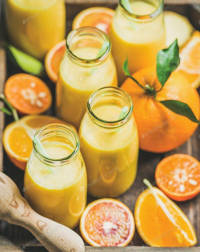 Gesunder gelber Smoothie in Flaschen mit frischen Früchten