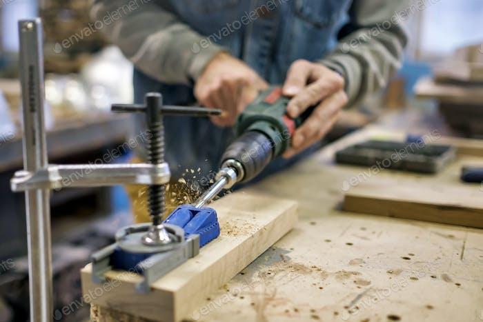 Caucasain man carpenter installs the furniture hinge. Pocket hole joinery concept.