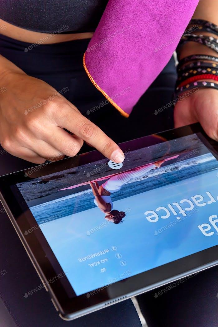 Frau beendet ihre Online-Yoga-Praxis auf ihrem Tablet zu Hause