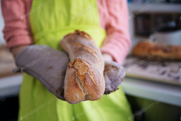 Woman in green apron holding her home made sourdough baguette
