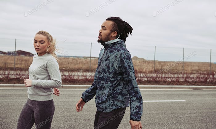 Diverse young couple finishing an outdoor run together