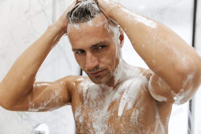 Close up of a confident man having a shower