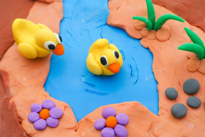 Two plasticine ducklings in a pond