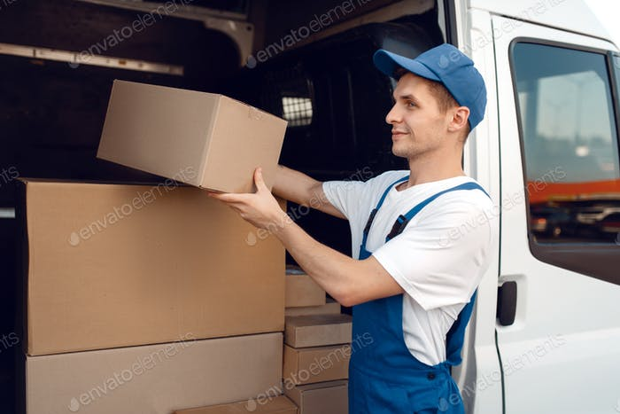 Smiling deliveryman with carton box at the car