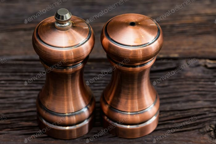 Salt and pepper in brown chrome casters on woodsen background