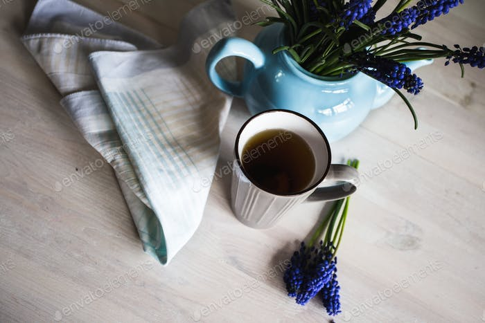Blue flowers in a teapot with a cup of tea on wooden background. Vintage