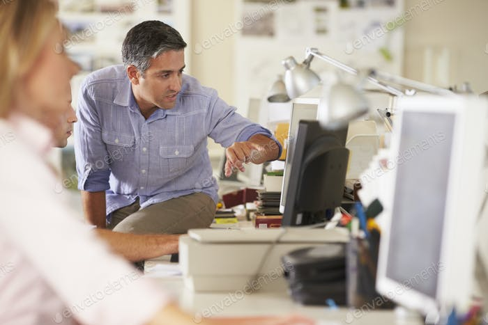 Workers At Desks In Busy Creative Office