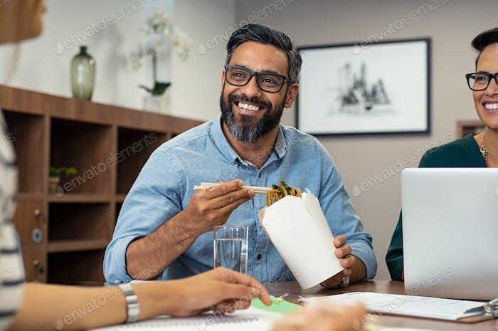 Businessman eating noodles during lunch break