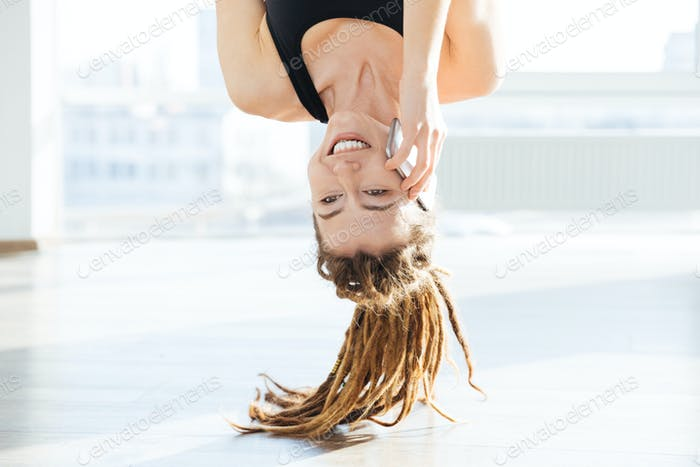 Upside down view of happy woman talking on mobile phone
