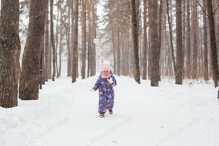 Child running in snowy forest. Toddler kid playing outdoors. Kid play in snowy park.