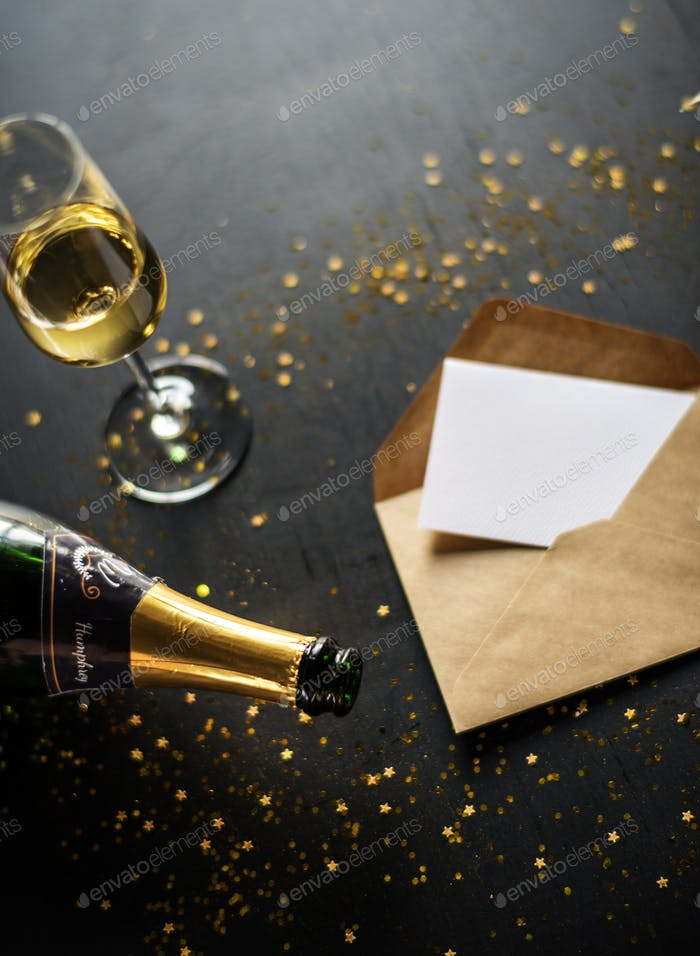 Celebration with champagne and card on black table