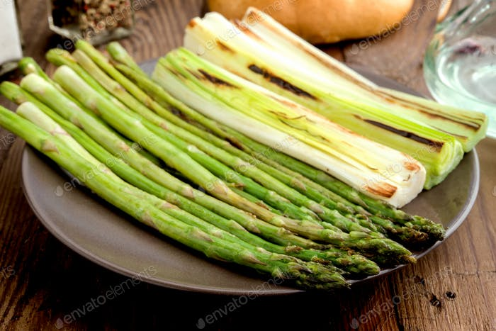 leeks and green asparagus roasted on the grill in square tray, on classic wood