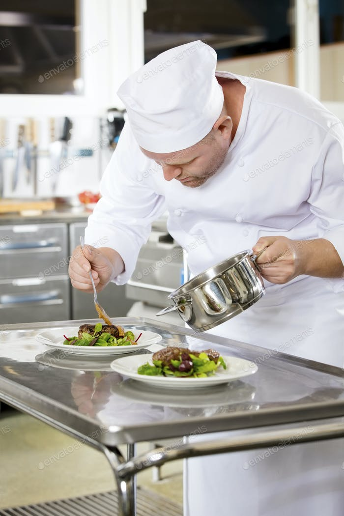 Professioneller Koch bereitet Fleischgericht im Restaurant zu