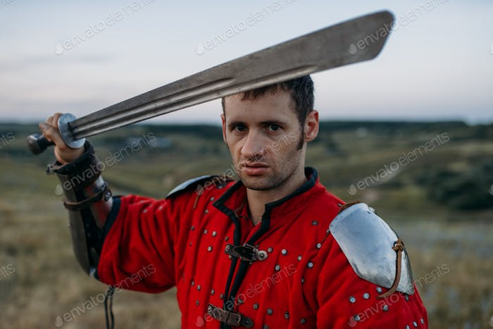 Medieval knight in metal helmet holds sword