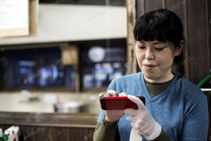 Smiling Japanese woman wearing one glove holding a red smart phone and checking messages.