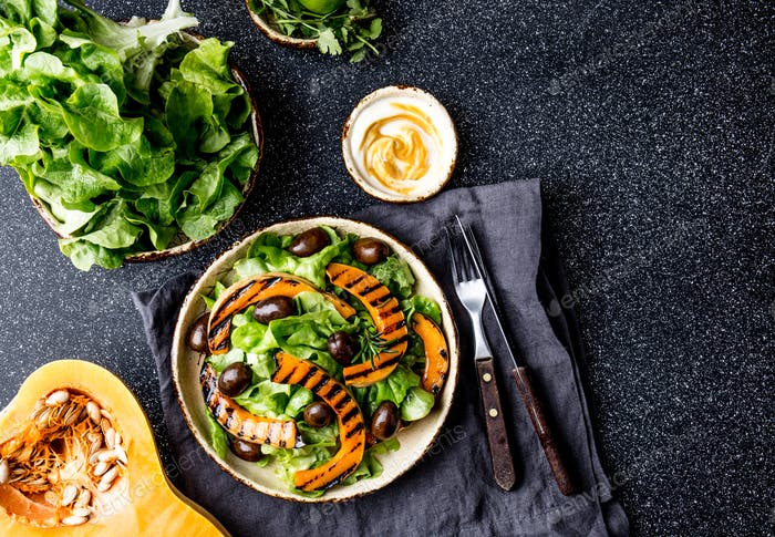 Grilled pumpkin and lettuce salad on dark background.