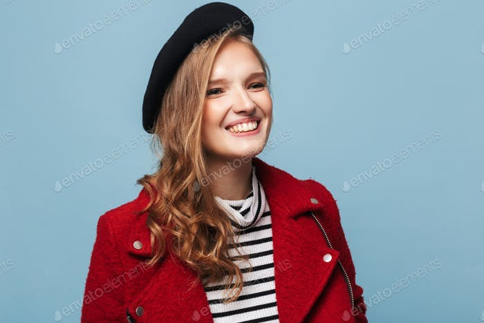 Young cheerful lady with wavy hair in black beret and red jacket happily looking aside