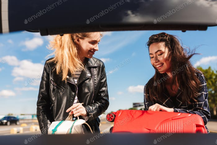 Two joyful girls happily folding suitcases into trunk of car in