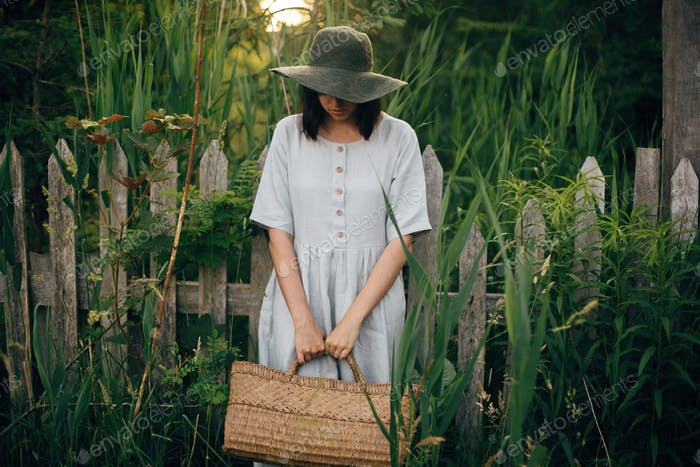 Stylish girl in linen dress holding rustic straw basket at wooden fence